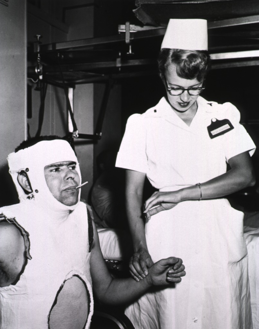 <p>A nurse takes the pulse of a male patient in a body cast.  The patient sits in a chair and has a thermometer in his mouth.</p>