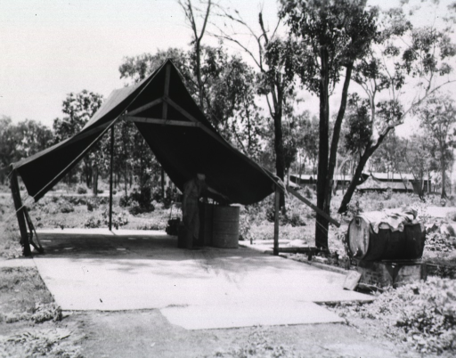<p>A serviceman stands under an open-air tent next to metal drums.  Other buildings can be seen in the distance.</p>
