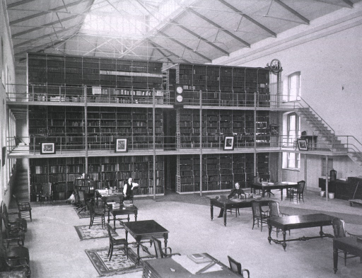 <p>Interior view: John Shaw Billings is sitting at a table in the middle of Library Hall; Thomas W. Wise sits at a desk resting his elbow on the back of the chair.  The three tier stacks are in the background, portraits are hanging off the second tier.  A book truck with a duster is on the ground floor. Tables and chairs are in the foreground of the reading room.  Windows run along the walls on all three tiers.  There appears to be a sky light.</p>