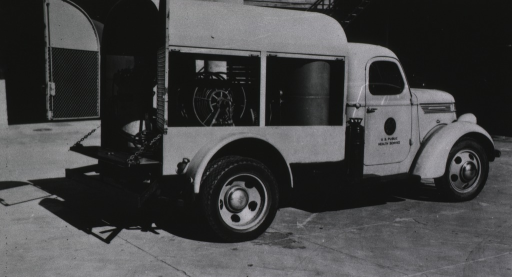<p>Right side view from rear of spray truck showing compressor, hose reel, and tank.</p>