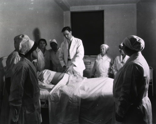 <p>In a maternity ward, a doctor demonstrates pelvic measurement techniques to midwives.</p>