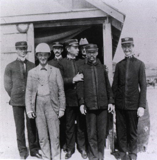 <p>Group of seven men posed at the entrance to a building.</p>