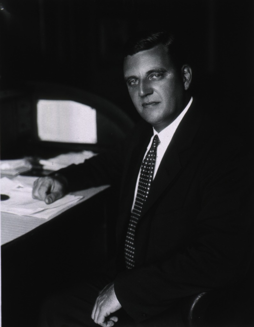 <p>Three-quarter length, full face, seated at desk.</p>