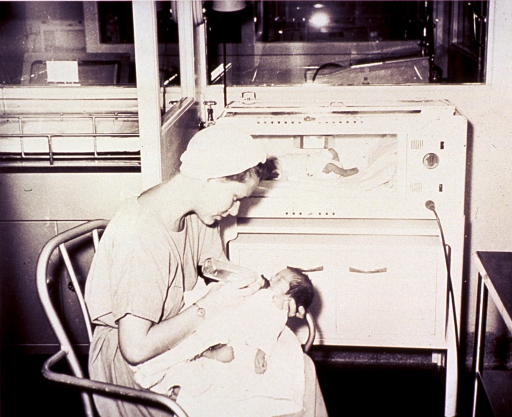 <p>A nurse wearing cap and hospital gown, feeds a premature infant; another infant is in an incubator in the background.</p>