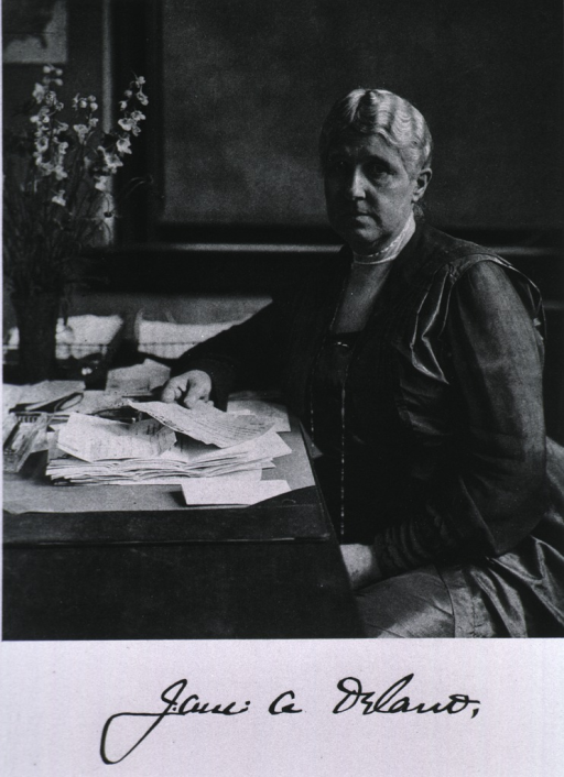 <p>Three-quarter length, seated at desk, holding paper in hand.</p>