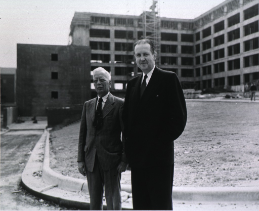 <p>Shown standing in front of a building under construction.</p>