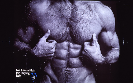 <p>Poster is a reproduction of a b&amp;w photo of a man's torso.  The man is covered in water droplets, as if stepping out of the shower, and has very well defined musculature.  Title and logo for publisher in lower left corner of poster.</p>