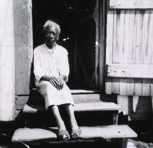<p>View of an old African American woman sitting on the wooden steps to her home.</p>