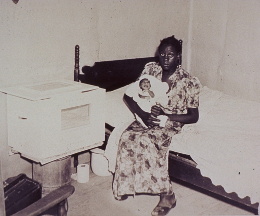 <p>A mother, sitting on a bed, is holding her premature infant; an incubator sits on a bucket at bedside.</p>