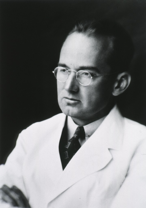 <p>Head and shoulders, left pose; wearing white lab coat and glasses.</p>
