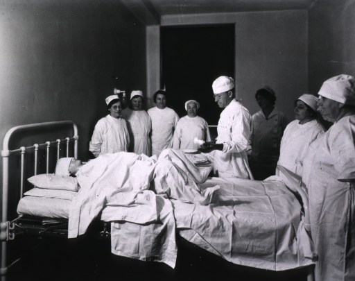 <p>Doctor, using a mannikin, demonstrates delivery techniques to midwives.</p>