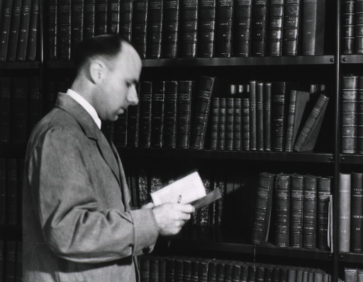 <p>Interior view: Robert B. Austin, of the reference division, is standing in front of the book stacks holding a pencil and an open book.</p>
