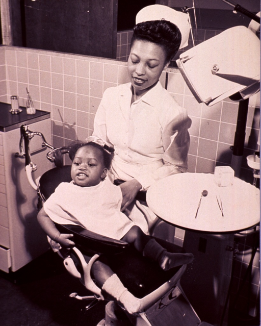 <p>An African American little girl is sitting in a dental chair with a dental assistant standing next to her.</p>