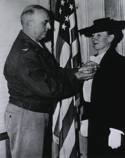 <p>Standing, 3/4 length, right pose, large hat, receiving medal of Freedom.</p>