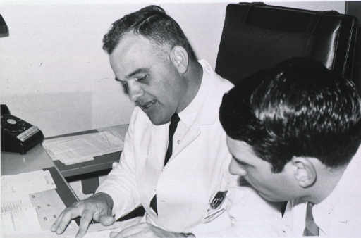 <p>Half-length, turned to left, wearing lab coat, at desk with papers, and an unidentified man in lab coat beside him.</p>