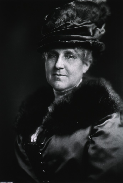 <p>Head and shoulders, full face, wearing fur trimmed coat and a hat with feathers.</p>