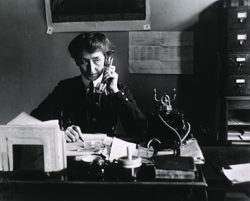 <p>Full face, seated at telephone.</p>