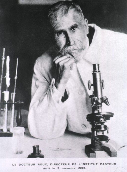 <p>Head and shoulders, full face; seated at table writing; microscope and test tubes to right side.</p>