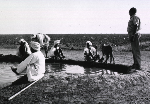 <p>Several men are sitting on the edge of a canal washing their feet; a plain stretches to the horizon behind them.</p>
