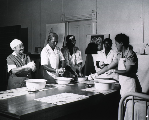 <p>Four African American nurse midwives receive instructions in cleanliness from Deola Lange Cyrus.</p>