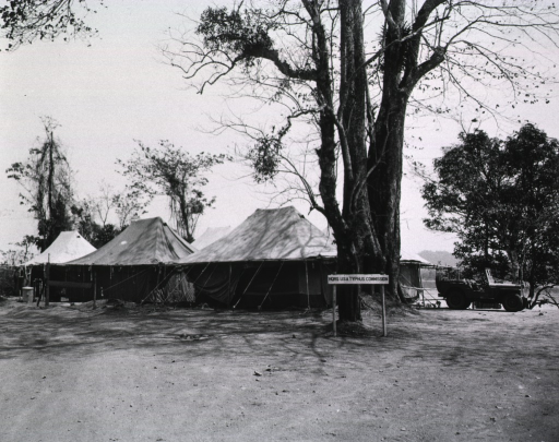 <p>One of three views (cf. nos. 3 and 4) of the headquarters of the U.S.A. Typhus Commission.  Three tents are pitched on a grassless bank abutting a body of water.  An army jeep is parked next to the tents.  In front of a large tree near the tents is a double-poled sign that reads: &quot;Hqrs U.S.A. Typhus Commission.&quot;  The location is unspecified.</p>