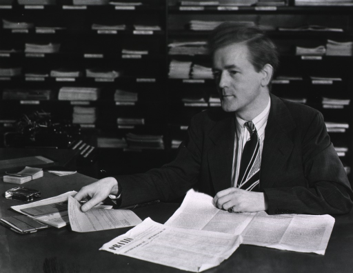 <p>Interior view: Allan Mackenzie is seated at a desk in front of the periodical shelves in the reference division reading room.  There is a typewriter between the desk and the stacks.</p>