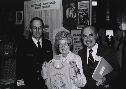 <p>Two men and a woman stand in front of an exhibit display of anti-smoking posters; the woman is holding up a tee shirt which says &quot;My Mommy Doesn't Smoke.&quot;</p>