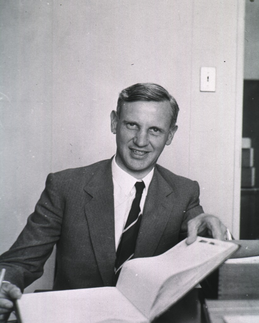<p>Half-length, full face, seated at desk, holding open book.</p>