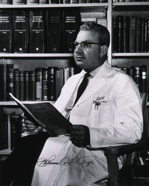 <p>Three-quarter length, seated, left pose, wearing white coat, holding medical journal, book shelves in background.</p>