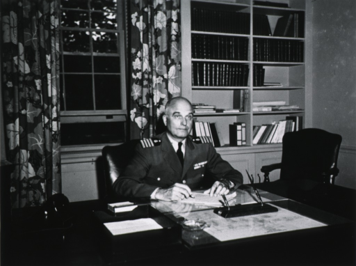 <p>Half-length, seated at desk, right pose, full face; wearing uniform, bookshelves in background.</p>