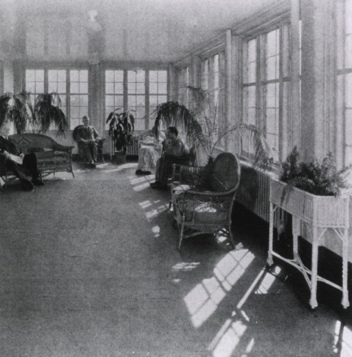 <p>A few patients and visitors sit in the solarium at Jeanes Hospital which is furnished with wicker furniture.</p>
