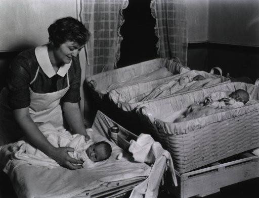 <p>A member of the Visiting Nurse Association tends to infants in a nursery.</p>