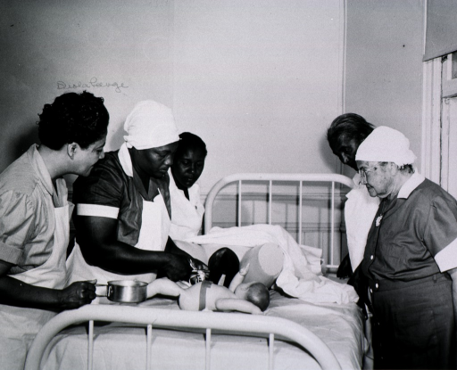 <p>View of four African American nurse midwives are practicing birthing techniques as Deola Lange Cyrus observes.</p>