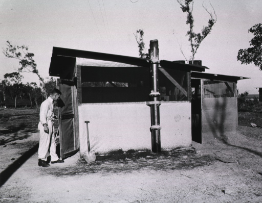 <p>A man is shown entering the free-standing latrine.  A shovel is propped next to the door of the latrine.</p>