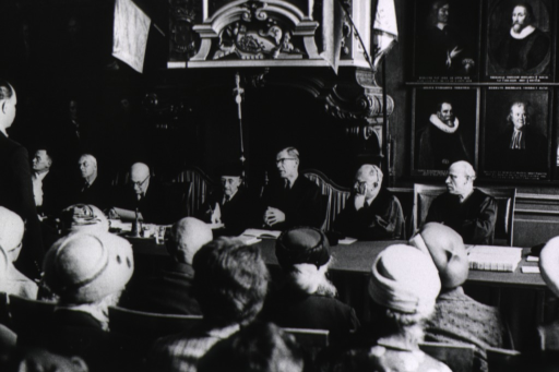 <p>Interior view: a doctoral candidate stands to the left before a panel of reviewers who are seated in front of a wall that is covered with the portraits of past professors at Leyden University. The audience fills the foreground.</p>