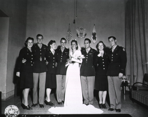 <p>A just-married couple stands next to three other couples and poses for the camera.  All but the bride are dressed in military uniforms.  On the wall behind the group are painted the U.S. and army flags, and the U.S. seal.</p>