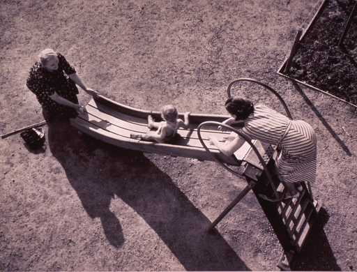 <p>Two women, a child, and a slide; one woman has sent the child on its way down the slide, the other woman waits at the end of the slide to catch the child.</p>