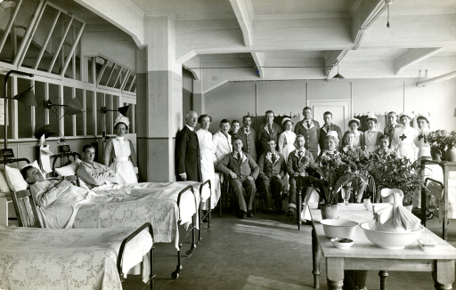 <p>Black and white photograph of a patient ward at King George Military Hospital, London, England. Dr. Lewis Smith is in the room with many patients, 2 of whom are laying in beds, nurses and physicans.</p>