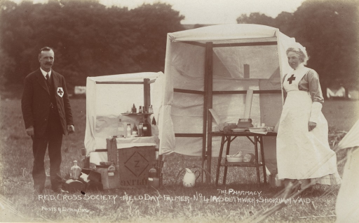 <p>Postcard featuring a black and white photograph of a Red Cross pharmacy in a field in Falmer, England. A man in a Red Cross uniform is on the left of the pharmacy and a Red Cross nurse stands on the right. Medicine and bottles are on tables in between them.</p>