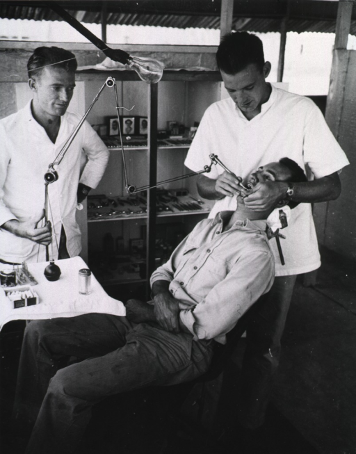 <p>Two dentists examine the teeth of a patient who sits back in a clinic.</p>