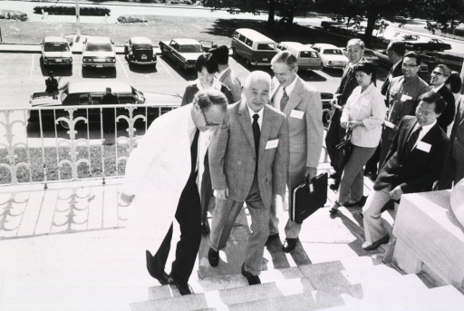 <p>Donald Fredrickson, director of the National Institutes of Health (NIH) and Qian Xinzhong, the People's Republic of China's minister of public health, are walking up the stairs to Building 1.  Dr. Fredrickson is in a lab coat.  There is a group of people walking behind them.  Cars are in the parking lot.</p>