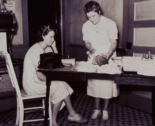 <p>Interior view of a kitchen: a nurse is instructing a young mother in the proper bathing techniques for her baby.</p>