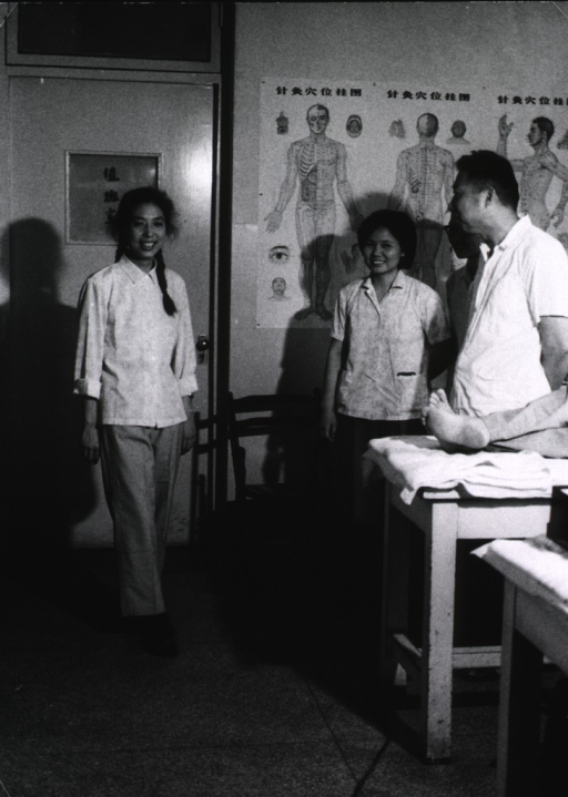 <p>Interior view: a young woman is walking across the room in a clinic; examination tables are to the right as are a few observers (parents and physician?); on the wall in the background are acupuncture charts.</p>
