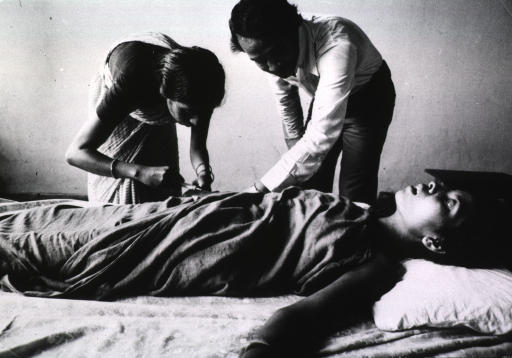 <p>A young woman is lying on a bed; a man is assisting a woman administer an injection.</p>