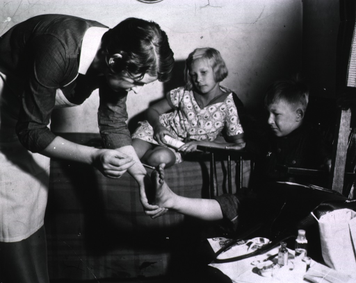 <p>A young boy winces in anticipation of pain as a member of the Visiting Nurse Association attends to his injured foot.  The boy's sister sits on a bed nearby.</p>