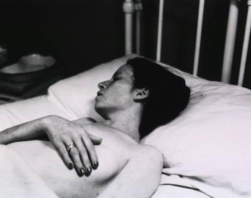 <p>A woman lies on a hospital bed with her face turned from the camera.  She covers her bared left breast with her hand.</p>
