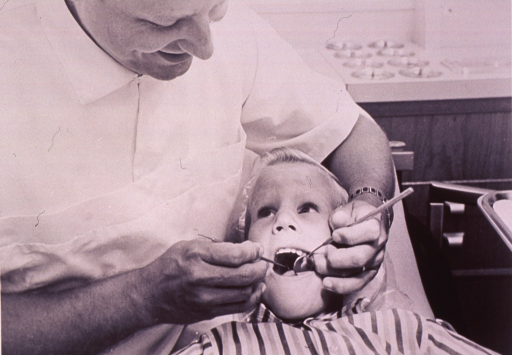 <p>A child is having his teeth examined by a dentist.</p>