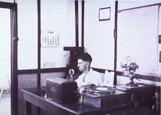 <p>A doctor is at a transceiver set in a base radio station.</p>