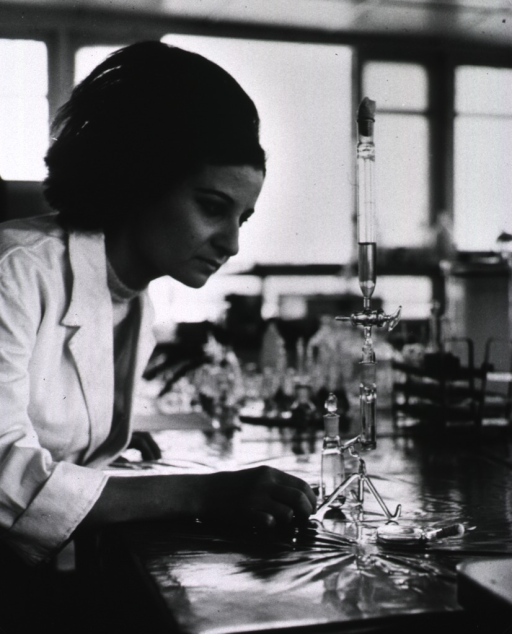 <p>A young woman using a glass apparatus in a laboratory to isolate the schistosoma parasite.</p>