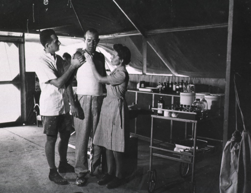 <p>A nurse and another medical assistant apply a cast to the torso of a standing serviceman.</p>